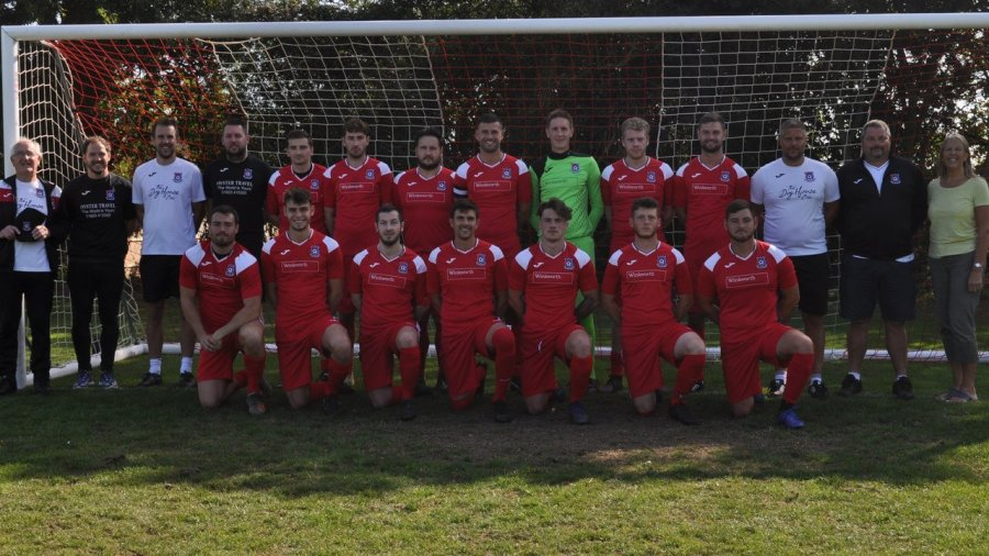yelverton fc first team in red kit in front of a goal